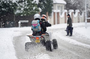 Winter weather: A couple use a quad bike to travel through the snow in Farnborough