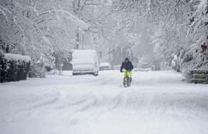Winter weather: A man attempts to cycle through the snow in Farnborough