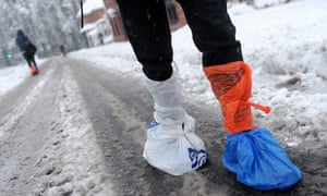 A pedestrian walks thorough snow with plastic bags tied over his shoes in Fleet, Hampshire