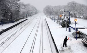 Winter weather: A woman tries to remove snow from a platform at a train station in Fleet