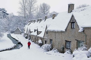 Winter weather:  A man walks through the snow past Arlington Row cottages