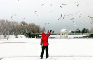 Winter weather: Blackpool, Lancashire, 5 January: Feeding the birds  on Stanley Park lake