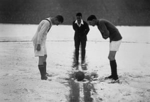 The referee tosses up on a snow-covered football pitch at the start of the football match between Arsenal and Manchester United.
