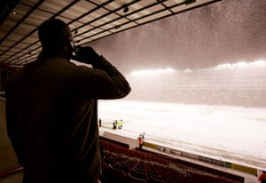 A fan makes a phone call while watching the snow fall prior to the Sheffield United v Crewe Alexandra match at Bramall Lane in March 2006