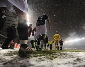 Players walk out onto the pitch as the snow falls ahead of the Barclays Premier League match between Stoke City and Fulham at The Britannia Stadium in January 2010