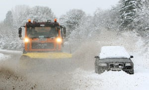 Winter weather: Hampshire: A snowplough passes an abandoned car on the A3