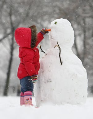 Winter weather: London:  A young girl makes a snowman at Highbury Fields