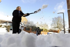 Winter weather: Kirby Hill, North Yorkshire: A woman clears snow from a road