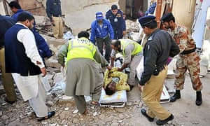 Pakistani volunteers remove a body from a collapsed house after an explosion in Karachi