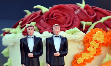 A wedding cake with statuettes of two men
