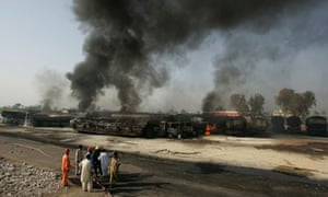 Pakistani firemen beside the tankers carrying fuel for Nato troops set alight by suspected militants