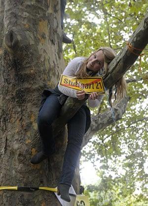 Stuttgart 21 Protest: Protestor sits in a tree showing a protest banner for Stuttgart 21