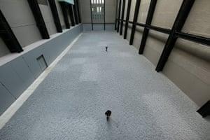 Turbine Hall: Workers rake the seeds of Artist Ai Weiwei's Installation 'Sunflower Seeds'