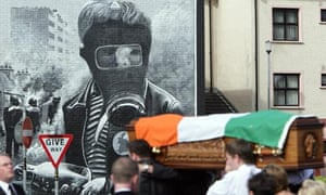 A Republican flag draped coffin passes a Bloody Sunday mural
