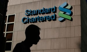 A  man walks pass the Standard Chartered Bank headquarters in Hong Kong.