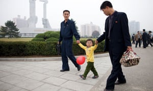 A family passes before the Party Foundation Monunment in Pyongyang.