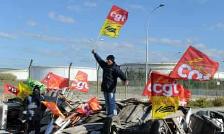 A striker holds a CGT union flag as strikers block fuel storage depots in Frontignan France.
