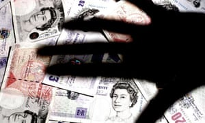 Shadow of hand over a pile of GBP banknotes