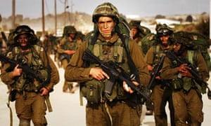 Israeli soldiers walk towards northern Gaza Strip