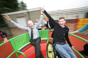 Teaching Awards 2010: A teacher and his student in a wheelchair enjoy a ride on a roundabout