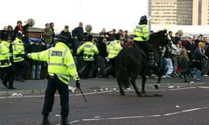 Fans are contained by police outside Old Trafford.