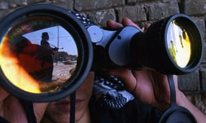 An insurgent from the Mahdi army is reflected in the binoculars of his fellow fighter