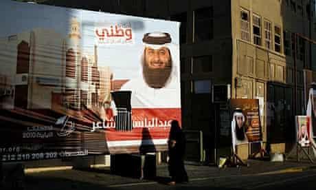 A Bahraini woman walks past election campaign billboards near Manama