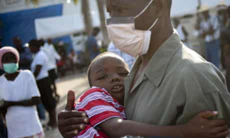 A man and a boy wait for medical attention in Haiti as cholera sweeps the earthquake ravaged island