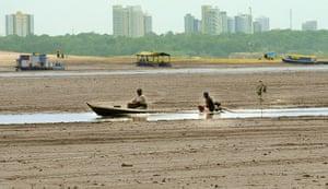 Amazonia drought: Two fishermen sail their boat