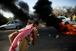 Israel Protest: An Israeli Arab boy passes by a fire during clashes in Umm el-Fahm