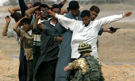 Iraqi men are frisked by a British soldier before being allowed to re-enter Basra