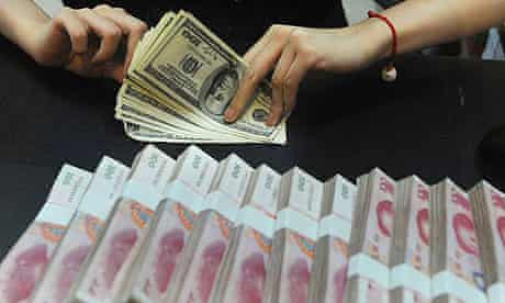 Employee counts US dollars next to Renminbi yuan banknotes at a bank in Hefei