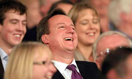 David Cameron listens to Lady Warsi's speech on day one of the Tory party conference in Birmingham