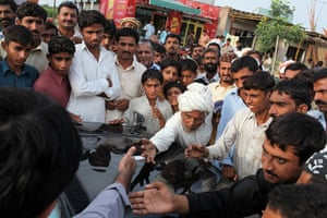 Pakistan floods- Punjab: A constituent reaches out to touch the hand of Jamshed Dasti