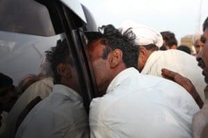 Pakistan floods- Punjab: A desperate flood affectee crowds into the car of Jamshed Dasti,