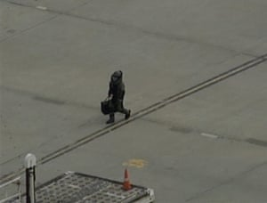 Cargo Terror: A bomb squad officer carries a package away from a UPS plane in Newark
