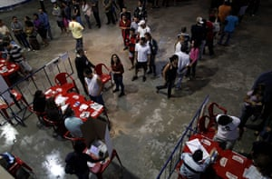 Brazil elections: People stand in line to vote in a polling station in the Rocinha slum