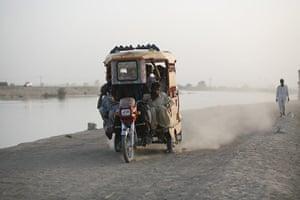 Sehwan Sharif Pakistan: A rickshaw travels along a canal embankment in Sehwan Sharif