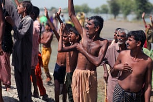 Sehwan Sharif Pakistan: Villagers wave to a Pakistani army helicopter dropping food aid