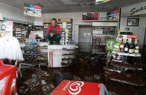 Hungary sludge flood: A shopkeeper squats on the counter of a flooded petrol station