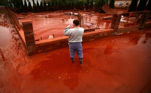 Toxic sludge Hungary: A man photographs red toxic mud from the sludge reservoir