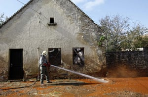 Toxic sludge Hungary: A Hungarian fire fighter cleans a street flooded with toxic mud in Devecse