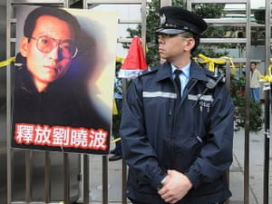 Liu Xiaobo Nobel Peace: A policeman standing next to a poster showing Chinese dissident Liu Xiaobo