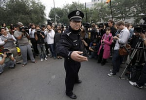 Liu Xiaobo Nobel Peace: A policeman gestures to reporters at the residence of Liu Xia