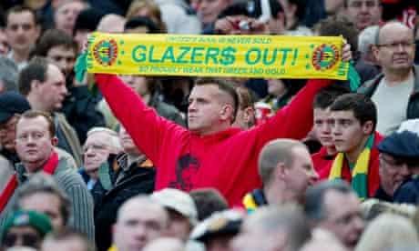 Manchester United fan holds up anti-Glazer scarf