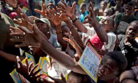 People reach out to catch books, donated by the Cuban government in Port-au-Prince, Haiti