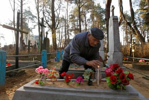 All saints day: Man lights candle on a grave at a cemetery in the village of Ivenets