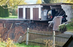 Germany sinkhole: Cars are seen parked in their garages next to the crater