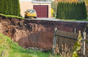 Germany sinkhole: A car parked in front of a house next to the crater