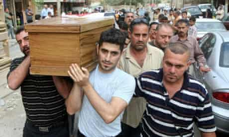 Iraqi Christians carry the coffin of a relative killed in baghdad church